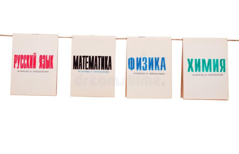 Gamla skolböcker på ett rep på vit arkivbild