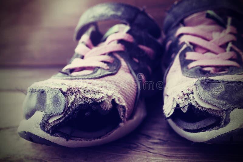 Gamla skor med slitna sjaskiga hemlösa kläder för hålskosnöre fotografering för bildbyråer