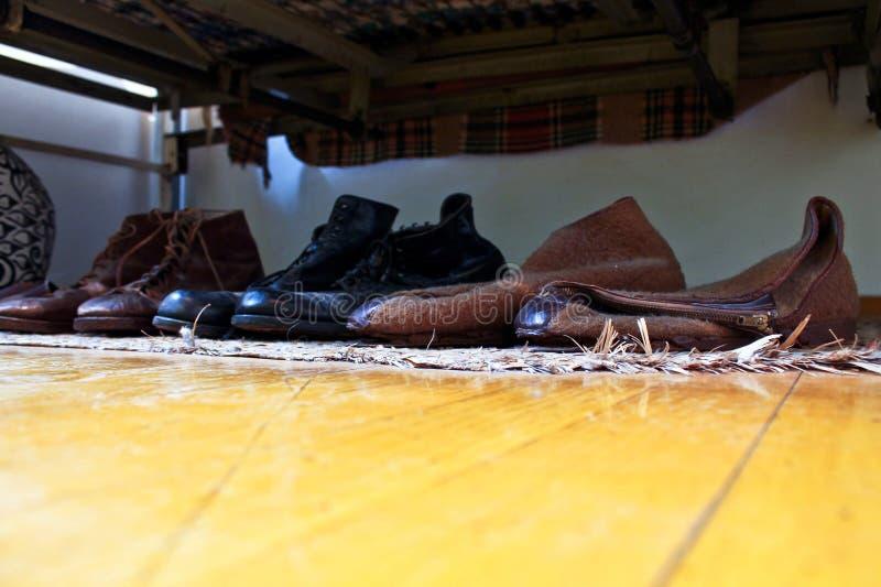 Gamla skor under någon säng royaltyfria bilder