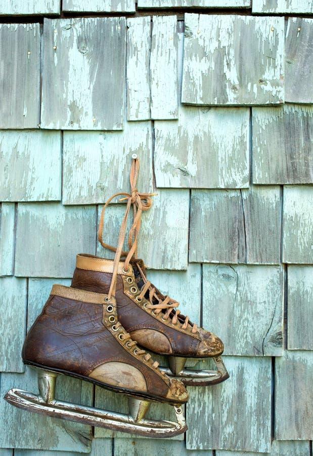 Gamla skridskor på en grungy vägg arkivbild