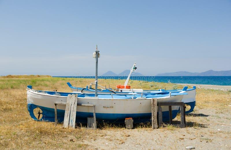 Gamla små fiskeskepp står på jordningen bredvid havet i Sicilien, Italien royaltyfri bild