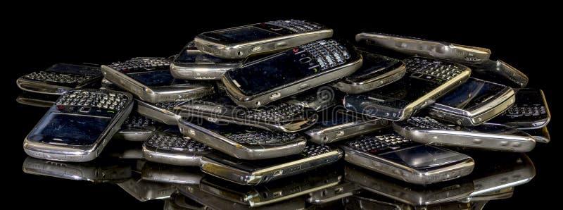 Gamla smarta telefoner i en hög som är klar för, återanvänder royaltyfria bilder