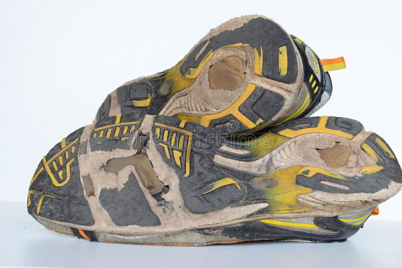 Gamla sportskor, gamla jogga skor, gamla gymnastikskor, slitna ut sportskor, gamla rinnande sportskor royaltyfri fotografi