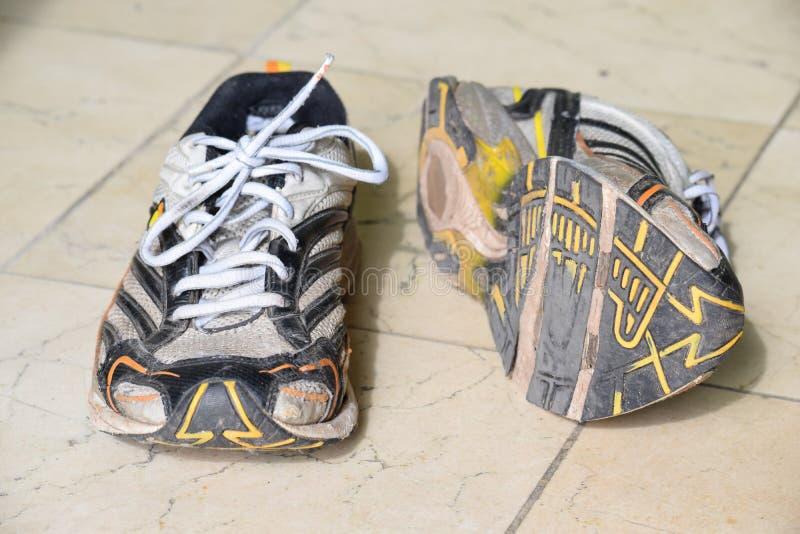 Gamla sportskor, gamla jogga skor, gamla gymnastikskor, slitna ut sportskor, gamla rinnande sportskor royaltyfria bilder