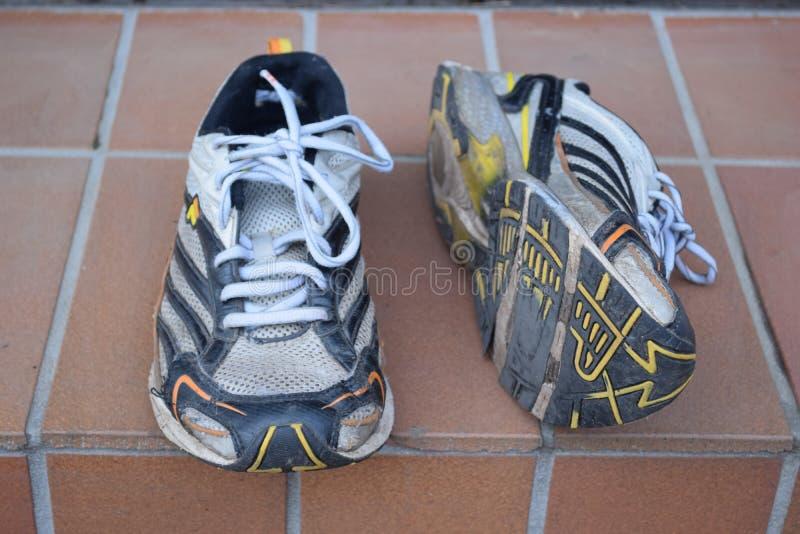Gamla sportskor, gamla jogga skor, gamla gymnastikskor, slitna ut sportskor, gamla rinnande sportskor arkivfoton