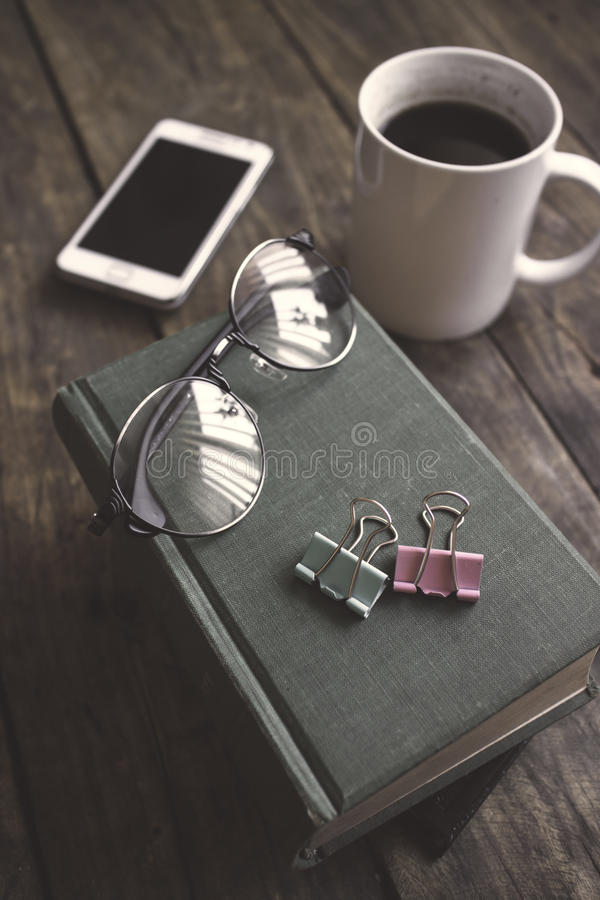 Gamla tappningböcker, smartphone och exponeringsglas på en trätabell royaltyfria foton
