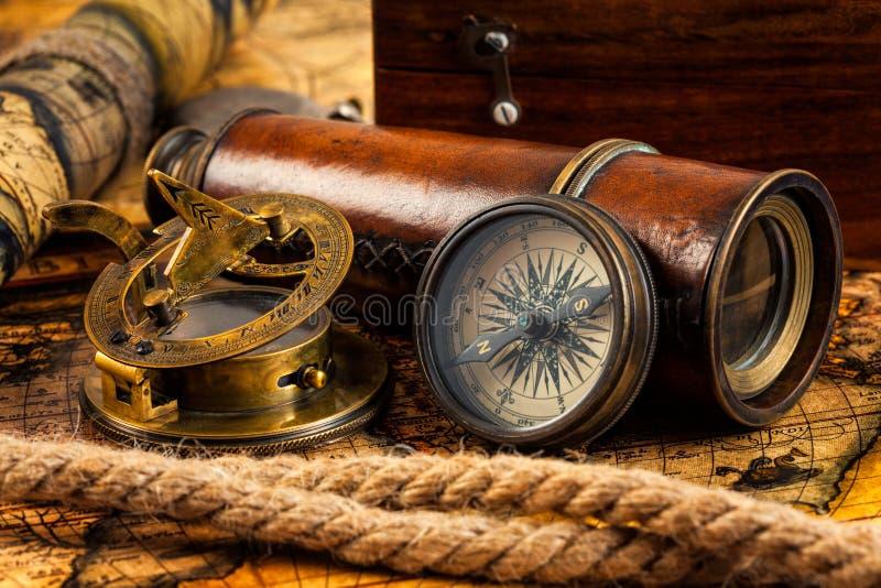 Gamla tappningkompass- och navigeringinstrument på forntida översikt royaltyfria bilder