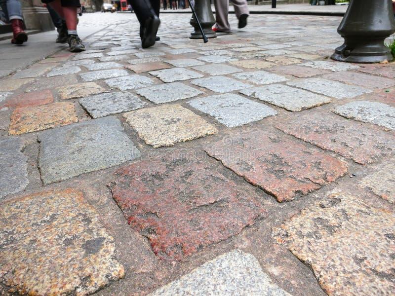 Gamla tegelplattor på trottoar och fot av gångare royaltyfri fotografi