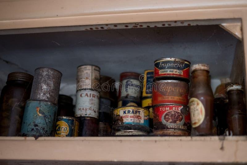 Gamla tenn av mat i skåp i kök i övergivet hus Harv UK fotografering för bildbyråer