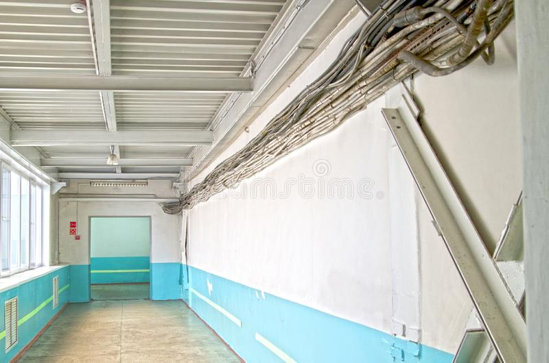 Gamla tjocka kablar som körs längs en vägg i korridoren av en industribyggnad Ryssland arkivbilder
