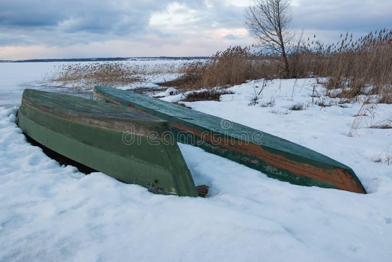Gamla träfartyg ligger i snön på kusten av entäckt djupfryst sjö i vintern royaltyfri bild