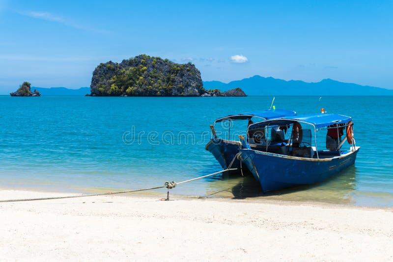 Gamla trägå fartyg som band repet på kusten på den tropiska stranden royaltyfria foton