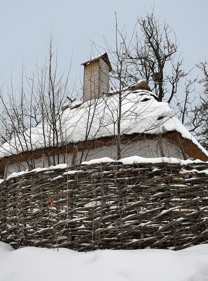 Gamla tr?hus under ett halmt?ckt tak som t?ckas med sn?- och vedtravest?llningen n?ra gamla tr?d arkivbilder