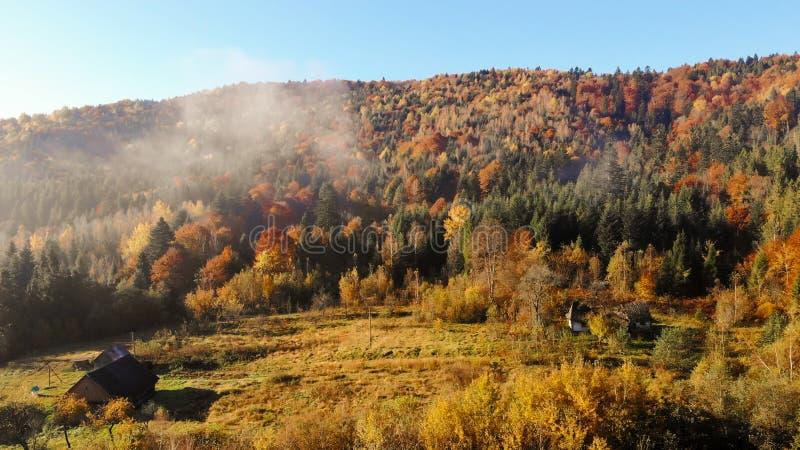 Gamla träkojor i dalen av Carpathian berg Höstlandskap, morgon royaltyfri foto
