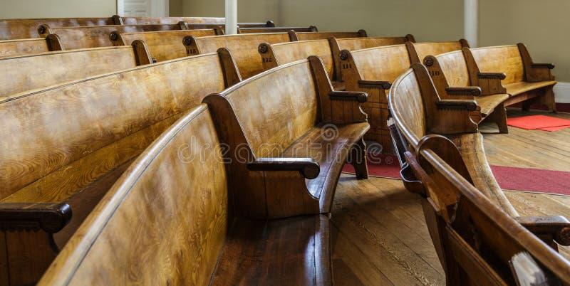Gamla träkyrkbänkar i kyrka royaltyfria foton