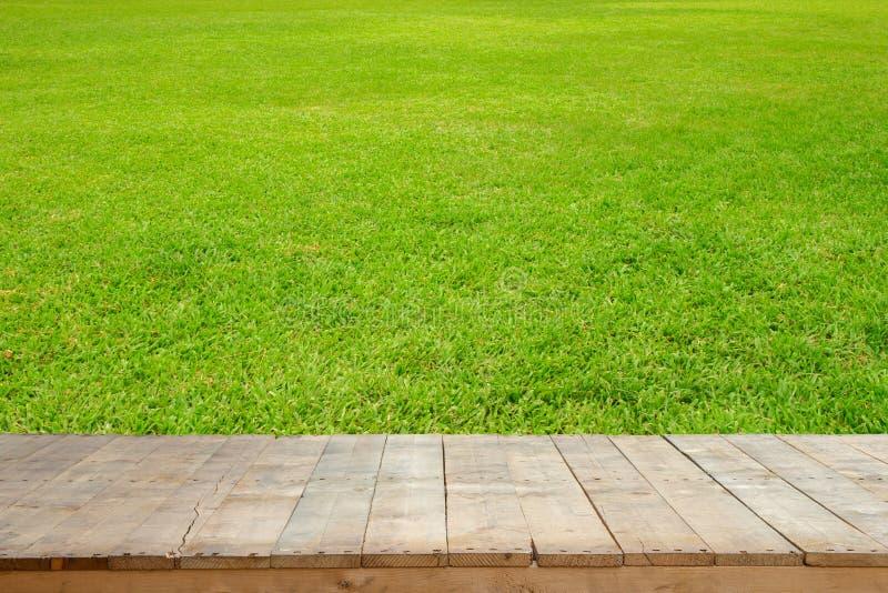 Gamla träplankor eller trätabell med grön gräsmatta för bakgrund royaltyfri foto