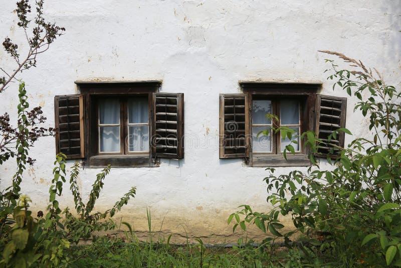 Gamla, traditionella fönster för byhus arkivfoto
