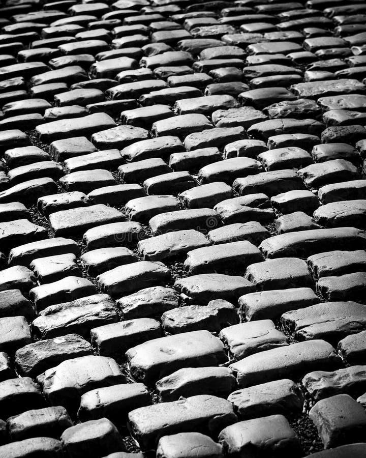 Gamla trottoartegelplattor i svartvitt arkivbilder