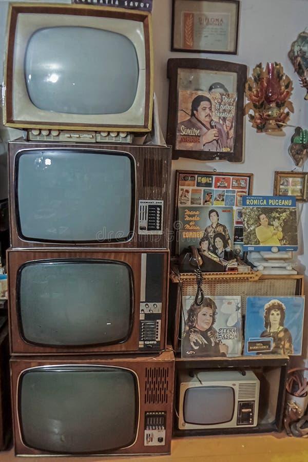 Gamla tv:ar och vinylmusikdisketter samlade i ett rum royaltyfri bild
