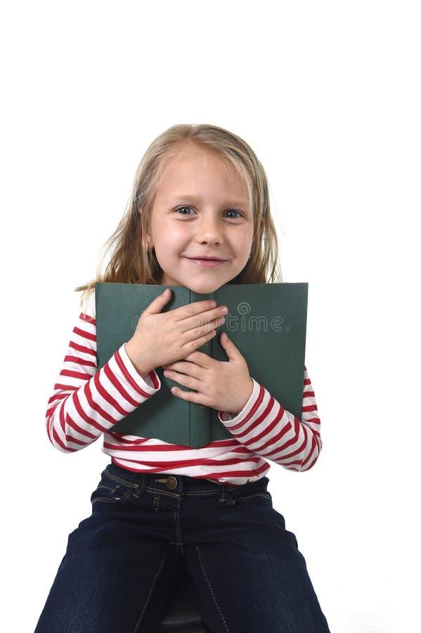 Gamla unga söta lite 6 eller 7 år med flickainnehavet för blont hår bokar att le som är lyckligt arkivfoton