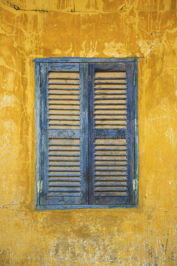 Gamla urblekta blått och gult lantligt fönster arkivbilder