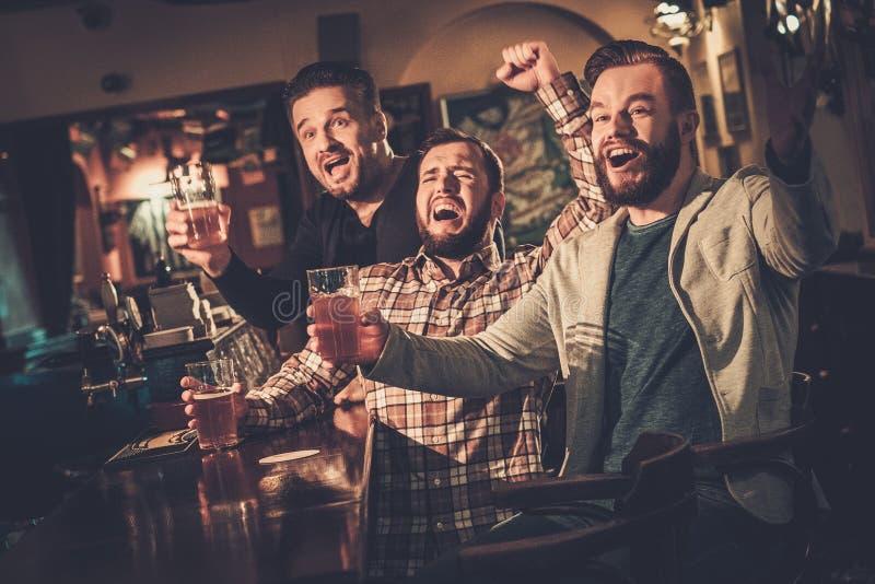 Gamla vänner som har gyckel som håller ögonen på en fotbolllek på TV och dricker utkastöl på stångräknaren i bar royaltyfri foto