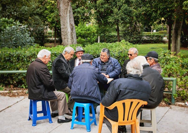Gamla vänner som spelar kort och skrattar i medborgareträdgård, parkerar royaltyfria foton