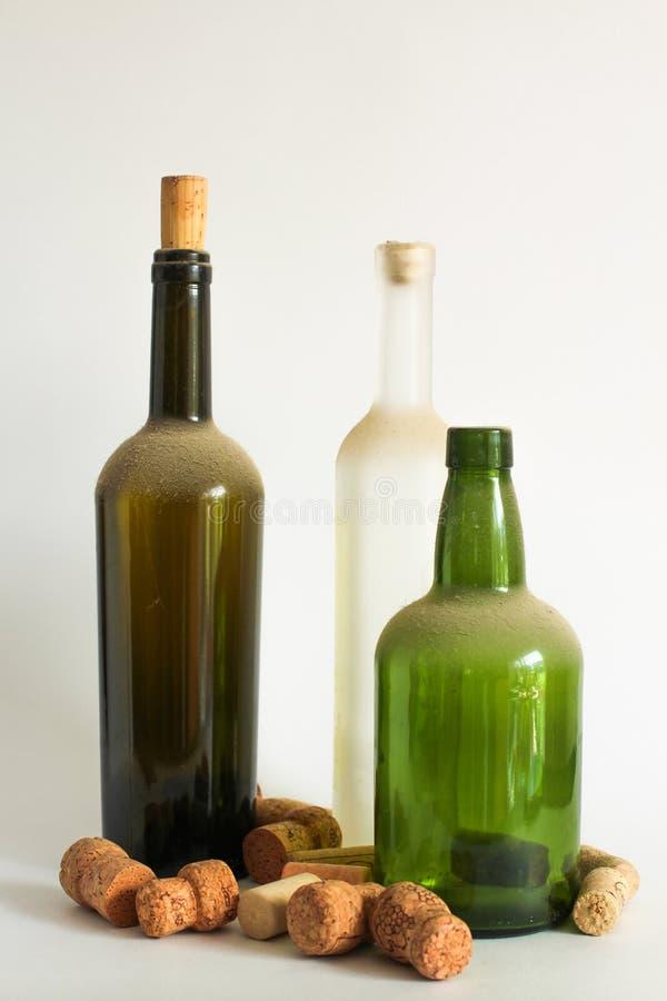 Gamla vinflaska och korkar för damm tre på vit arkivfoto