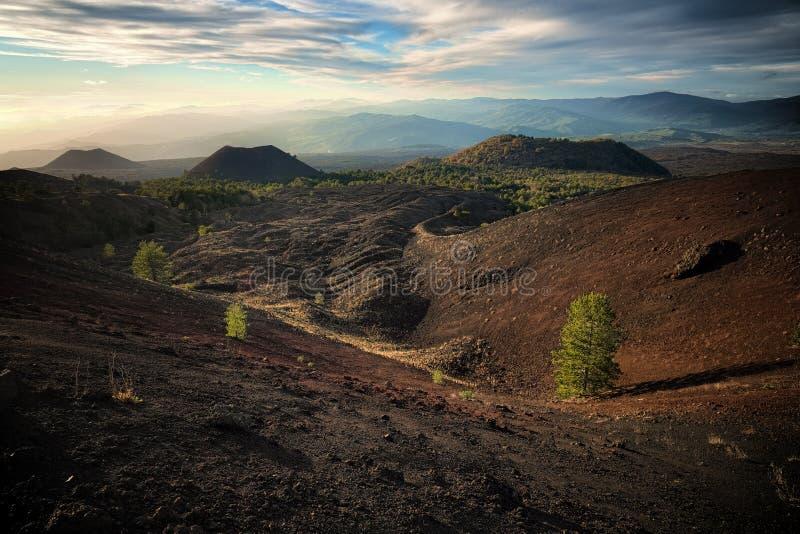Gamla vulkaniska kottar på skymning arkivfoton