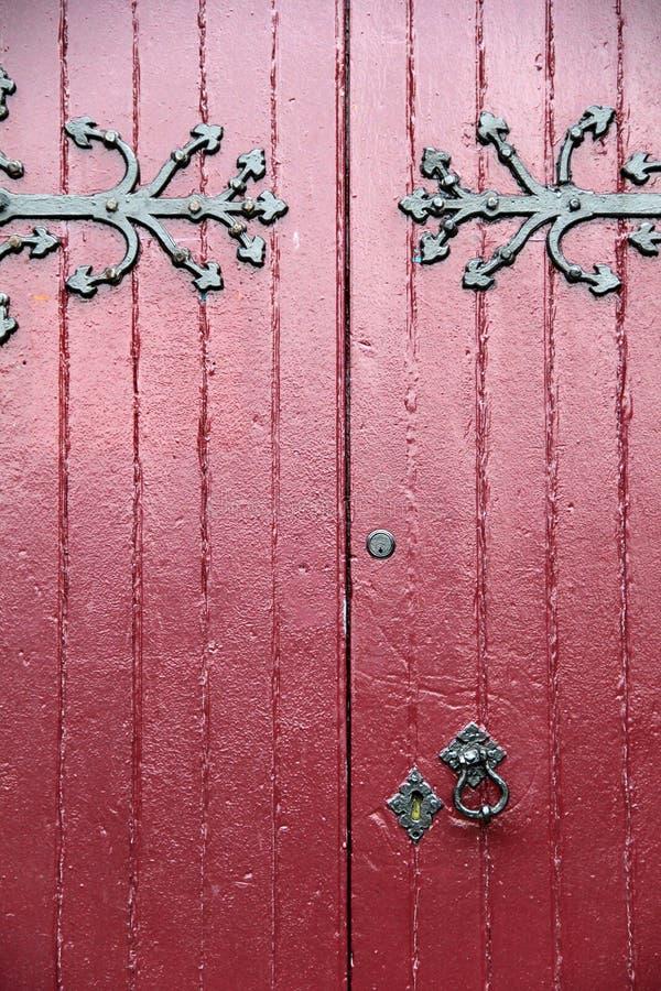 Gamla wood dörrar i skuggor av rödbrunt, med skurkrollsvartmaskinvara royaltyfri fotografi