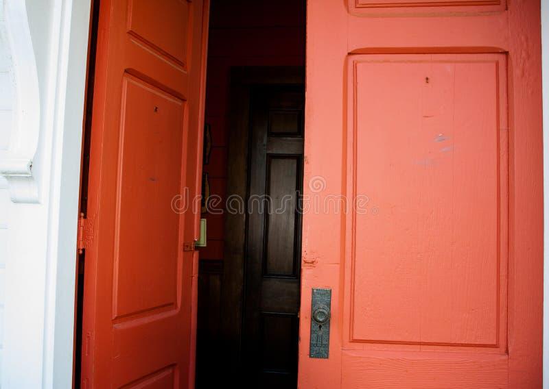 Gamla wood röda dubbla dörrar som in leder till en mörk korridor arkivbilder
