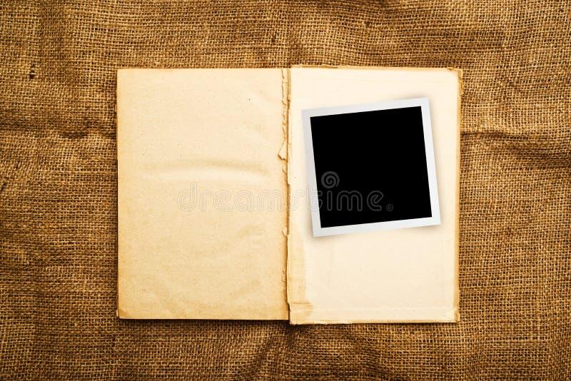 Gammal öppen bok med fotoramen royaltyfria foton