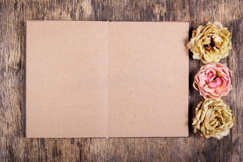 Gammal öppen personlig dagbok med tomma ark och vissna rosor Döda rosor och en gammal bok royaltyfri foto
