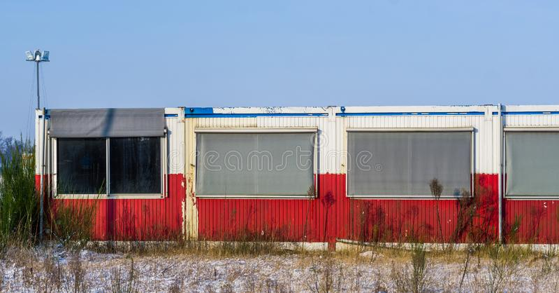 Gammal övergiven behållarebyggnad med fönster i mitt av ingenstans fotografering för bildbyråer