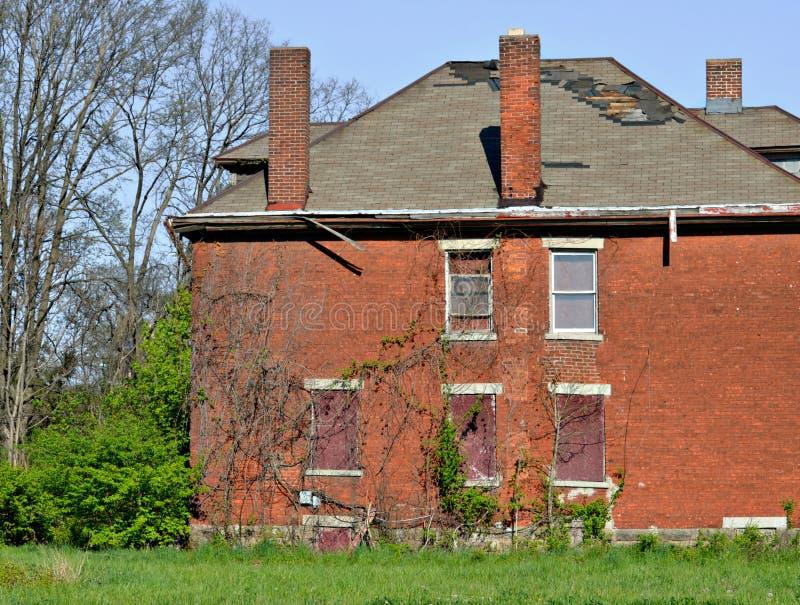 Gammal övergiven egenskap för tegelsten för två berättelse bostads- royaltyfri fotografi