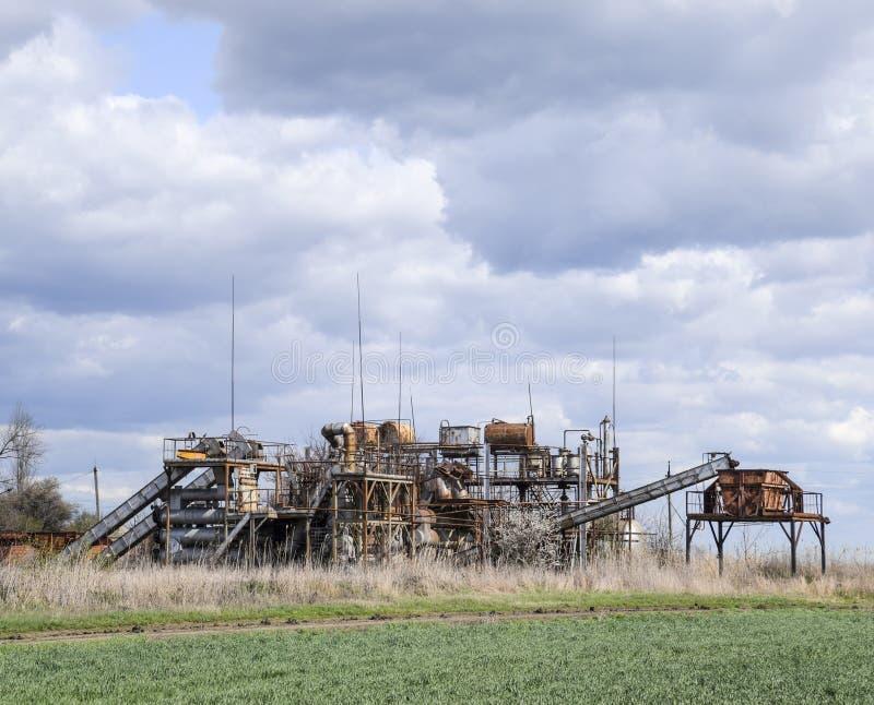 Gammal övergiven eterisk växt Rostad utrustning för destillationen av nödvändiga oljor gammal övergiven fabrik royaltyfria bilder