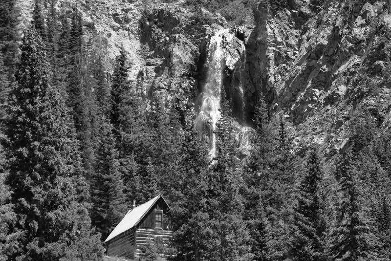 Gammal övergiven journalkabin med vattenfallet fotografering för bildbyråer
