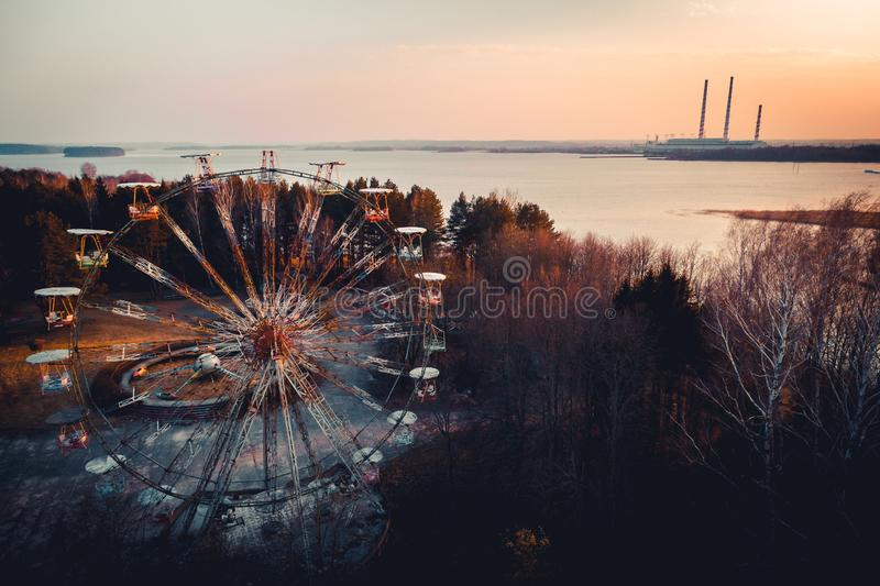 Gammal övergiven karusell för ferrishjul framme av kraftverklampglas Övergav detta parkerar är i den Elektrenai staden i Litauen, fotografering för bildbyråer