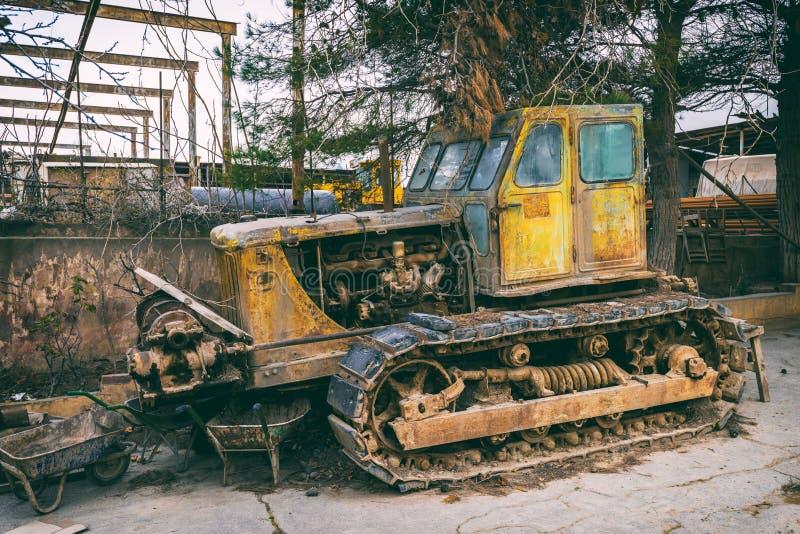 Gammal övergiven traktor i gård arkivfoto