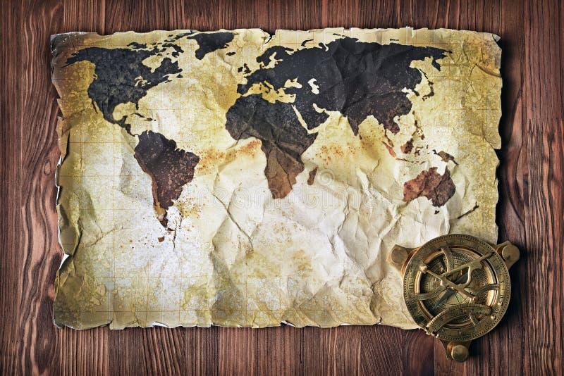 Gammal översikt av världen på gult retro nedfläckat papper med tappningkompasset royaltyfria bilder