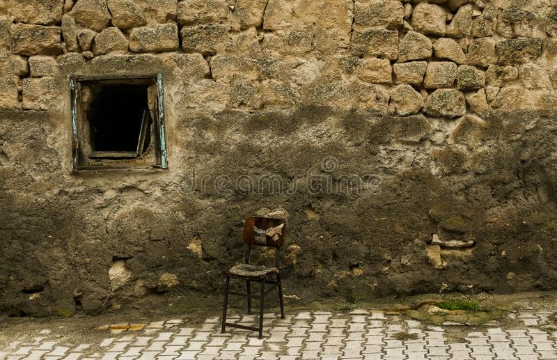 Gammal adandoned stol framme av den gamla avbrottsväggen i gatan royaltyfria bilder