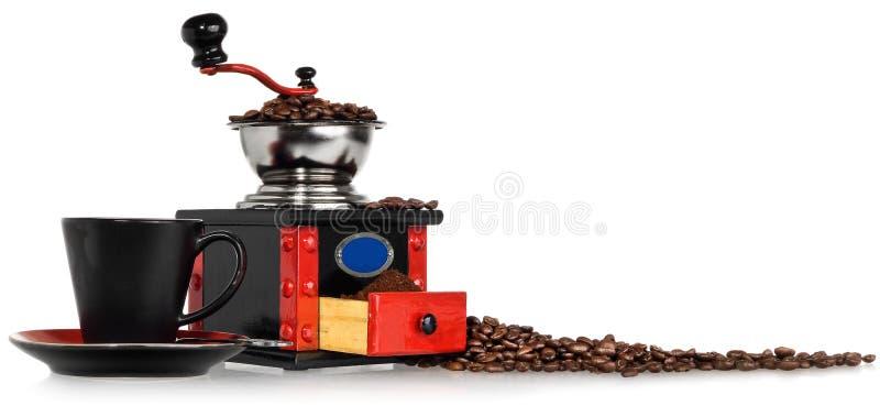 Gammal antik träsvart och röd kaffekvarn, kopp och spillt arkivbild