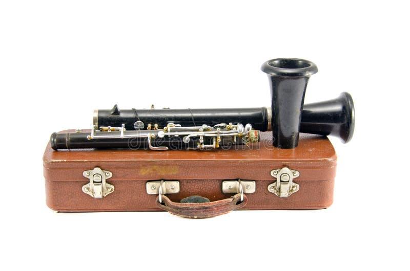 Gammal använd klarinett på den bruna läderasken som isoleras på vit arkivbild