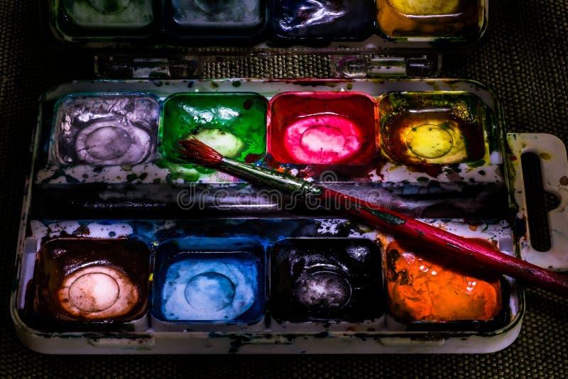 Gammal använd makro fortfarande l för vattenfärgmålarfärgask och borstenärbild arkivfoton
