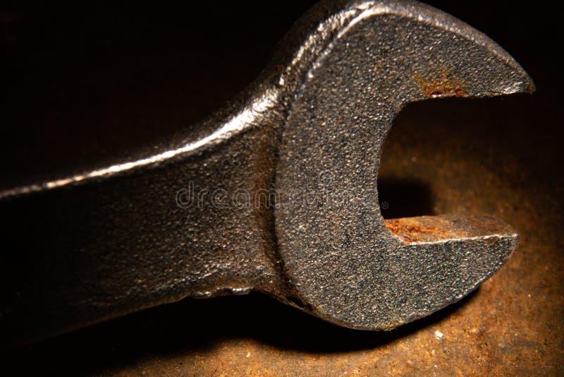 Gammal använd metallskiftnyckel i grungebelysning royaltyfria foton