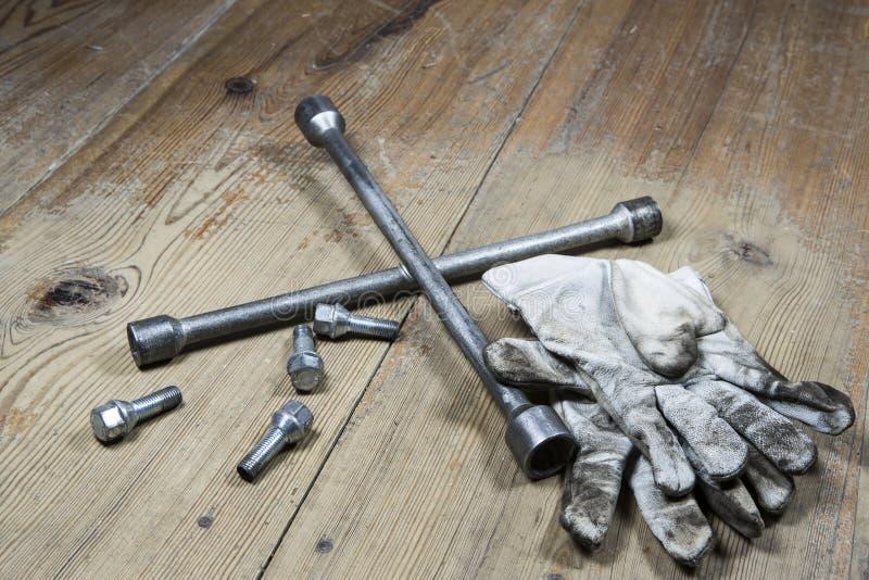 Gammal använd skiftnyckel med skruven och smutsiga handskar arkivbild