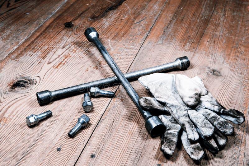 Gammal använd skiftnyckel med skruven och smutsiga handskar royaltyfri fotografi