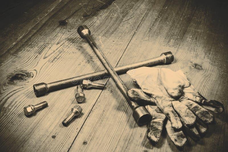 Gammal använd skiftnyckel med skruven och smutsiga handskar arkivbilder