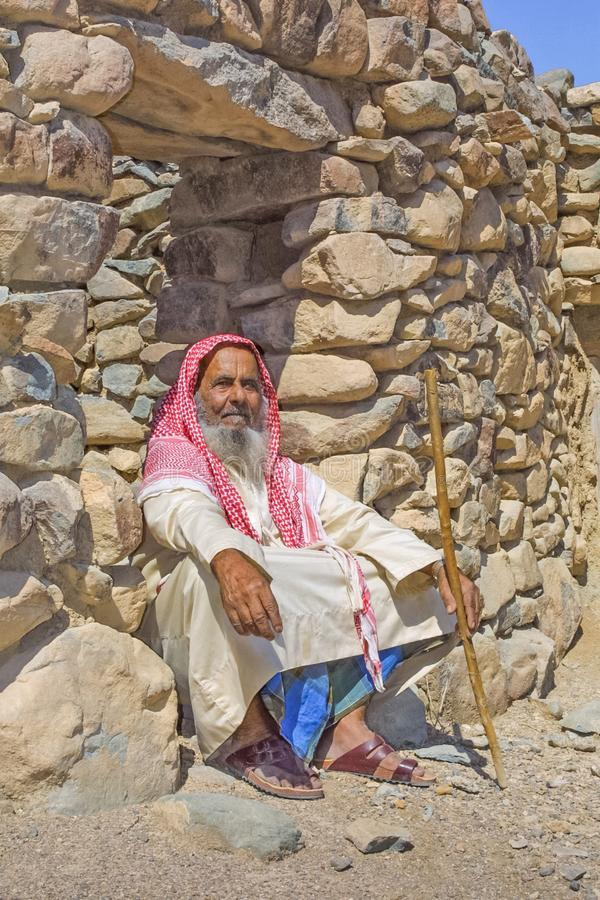 Gammal arabisk man utanför stenboning fotografering för bildbyråer