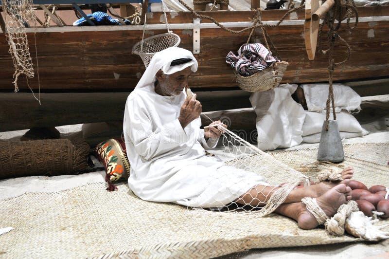 Gammal arabiska Sailer som arbetar på netto på den Abu Dhabi International Hunting och ryttareutställningen 2013 royaltyfria foton